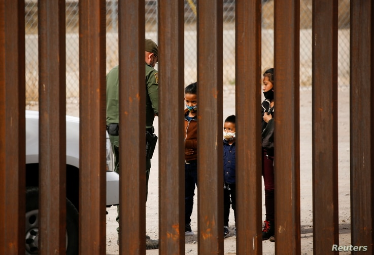 Migrants are detained by a U.S. Border Patrol agent after crossing the Rio Bravo river to turn themselves in to request for...