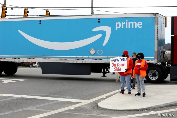 FILE PHOTO: People hold a banner at the Amazon facility as members of a congressional delegation arrive to show their support...