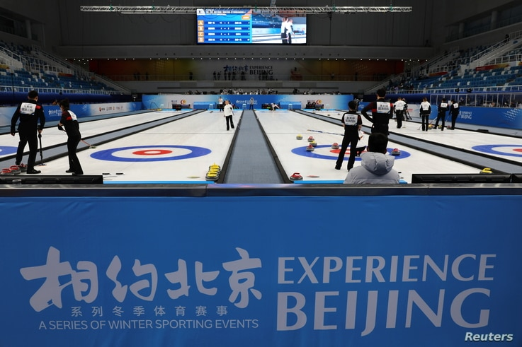 Athletes take part in a curling competition held as a test event for the 2022 Olympic Winter Games, at the National Aquatics...