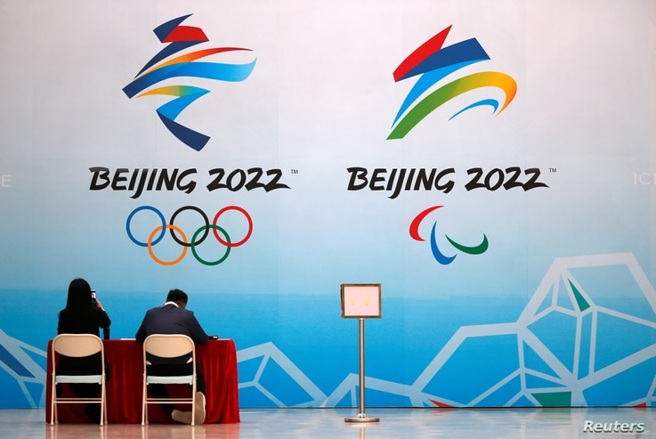 Staff members sit near a board with signs of the 2022 Olympic Winter Games, at the National Aquatics Center, known colloquially...