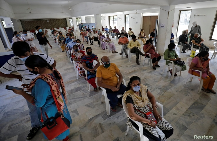 People sit in a waiting area to receive a dose of COVISHIELD, a coronavirus disease (COVID-19) vaccine manufactured by Serum...