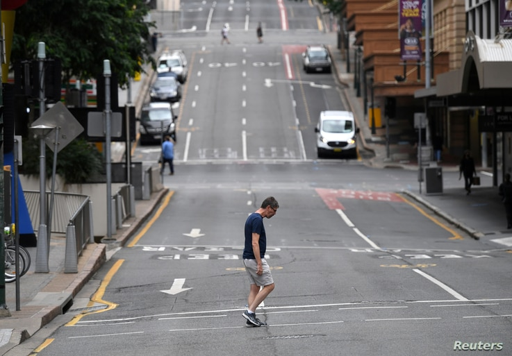 FILE PHOTO: A man crosses a mostly empty city centre street as people in Greater Brisbane have been ordered into lockdown as…