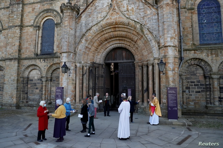 Dean of Durham Andrew Tremlett greets members of the congregation following the Easter Sunday Eucharist service at Durham…