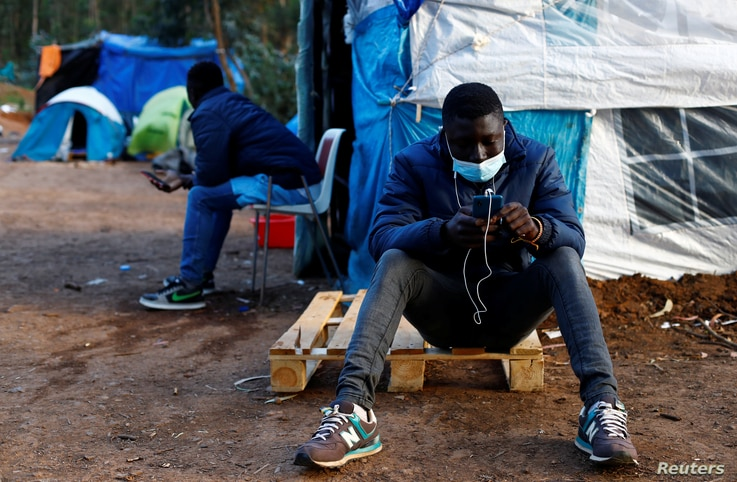 Two migrants are photographed together in the tents where they have lived for weeks in La Laguna, on the island of Tenerife.