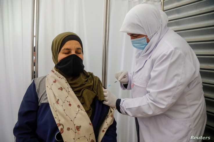 A Palestinian member of education staff receives a dose of Sinopharm vaccine against the coronavirus disease (COVID-19) as...