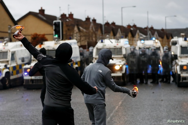 Rioters throw burning bottles at the police on the Springfield Road as protests continue in Belfast, Northern Ireland April 8,…