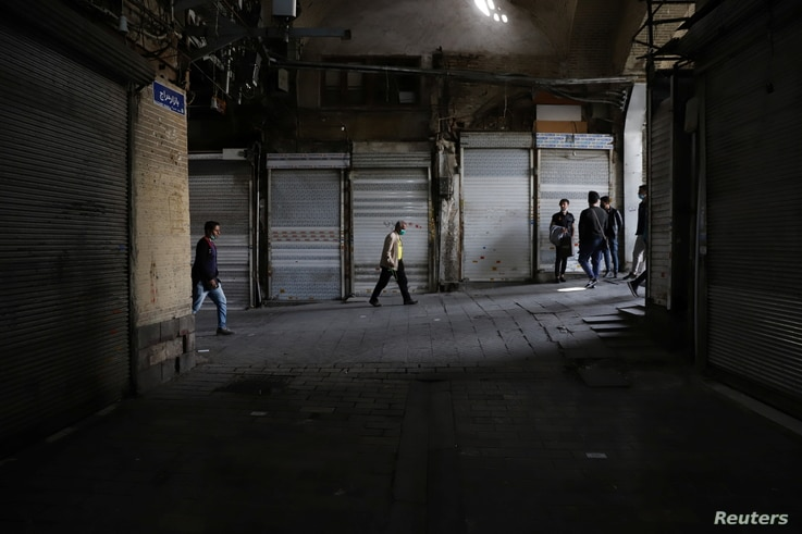People walk next to closed shops of Tehran Bazaar following the tightening of restrictions to curb the surge of COVID-19 cases,...