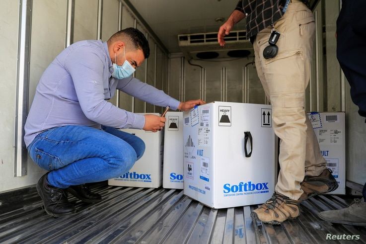 Personnel check the first shipment of the Pfizer's vaccine against the coronavirus disease (COVID-19) at Baghdad International...