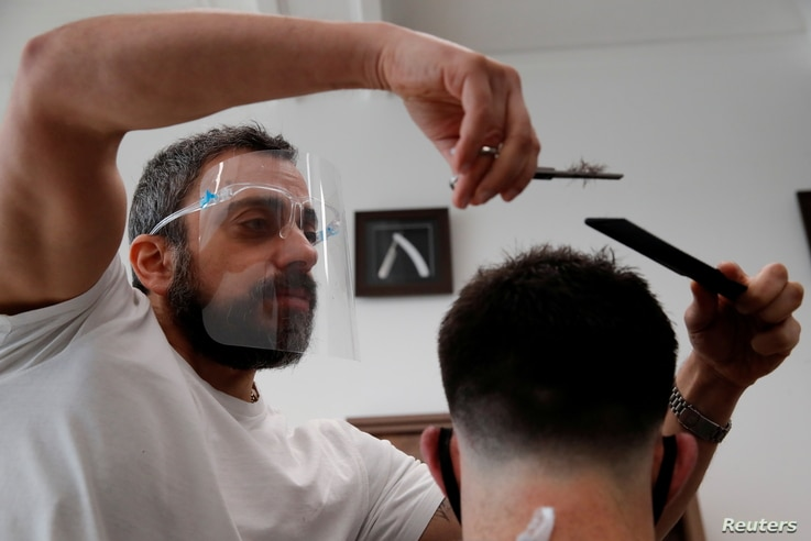 Chris, owner of Stag Co barbers, cuts hair as hairdresser shops reopen, as the coronavirus disease (COVID-19) restrictions ease…