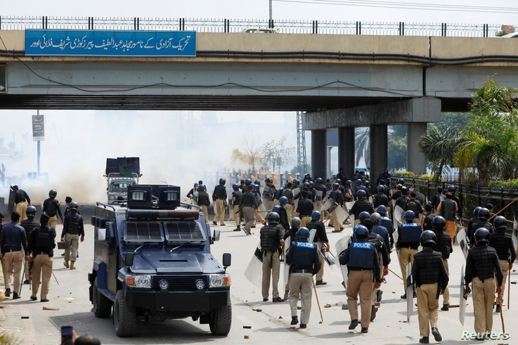 Police officers fire teargas as they move to disperse the supporters of the Tehreek-e-Labaik Pakistan (TLP) Islamist political…