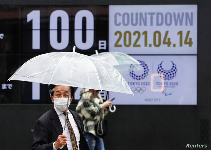 Passersby walk past a screen showing a countdown to the Tokyo 2020 Olympic Games and Tokyo 2020 Paralympic Games that have been…