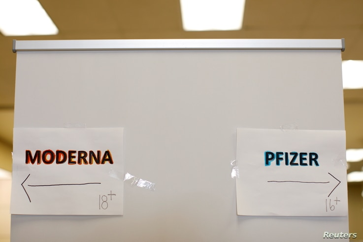 FILE PHOTO: Signs and age groups are shown for the Pfizer and Moderna vaccines at a vaccination center as California opens up...