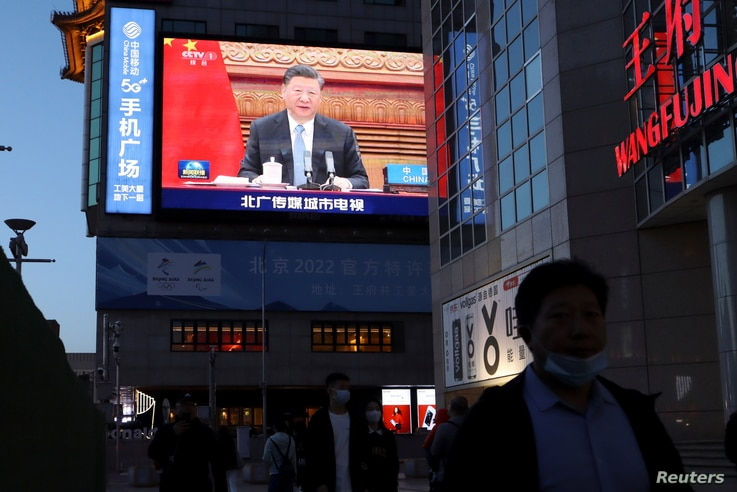 A giant screen shows news footage of Chinese President Xi Jinping attending a video summit on climate change.