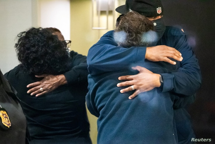 People embrace after learning that their loved one was safe after a mass casualty shooting at the FedEx facility in...