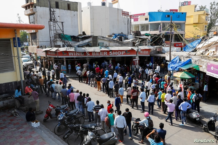 People queue outside a wine store to buy liquor after Delhi government ordered a six-day lockdown to limit the spread of the...