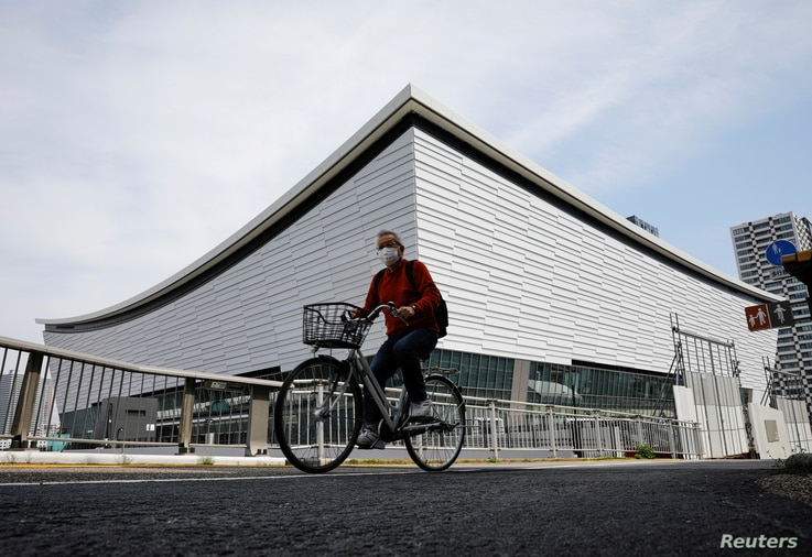 FILE PHOTO: A man wearing a protective mask amid the coronavirus disease (COVID-19) outbreak cycles past Ariake Arena  in Tokyo…