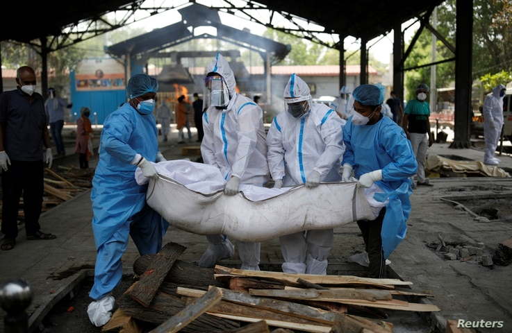 Health workers and relatives wearing personal protective equipment (PPE) carry the body of a man, who died from the coronavirus…