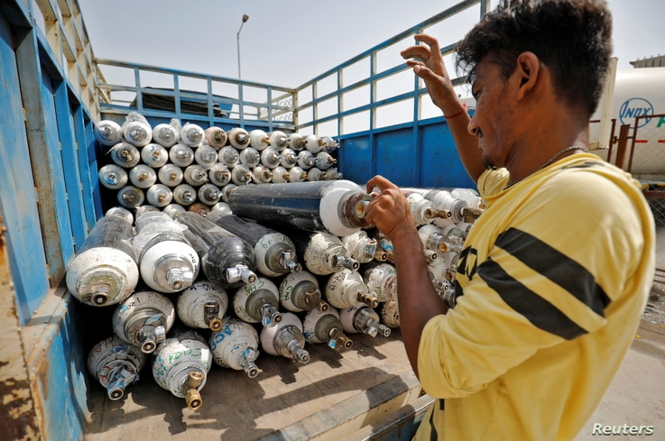 A worker loads empty oxygen cylinders onto a supply van to be transported to a filling station, at a COVID-19 hospital, amidst the spread of the coronavirus disease (COVID-19) in Ahmedabad, India, April 22, 2021.