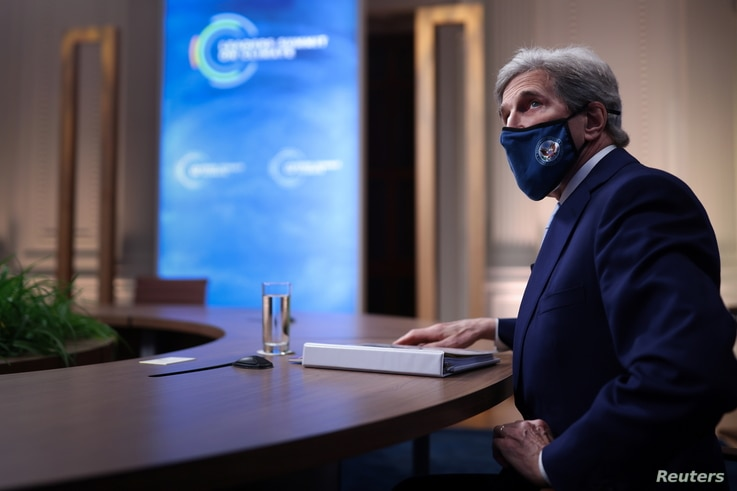 John Kerry, Special Presidential Envoy for Climate, looks up at a video screen while participating in a virtual Climate Summit.