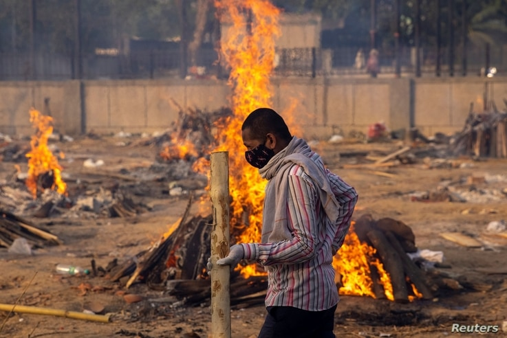 A man walks past burning funeral pyres of people, who died due to the coronavirus disease (COVID-19), at a crematorium ground in New Delhi, India, April 22, 2021.