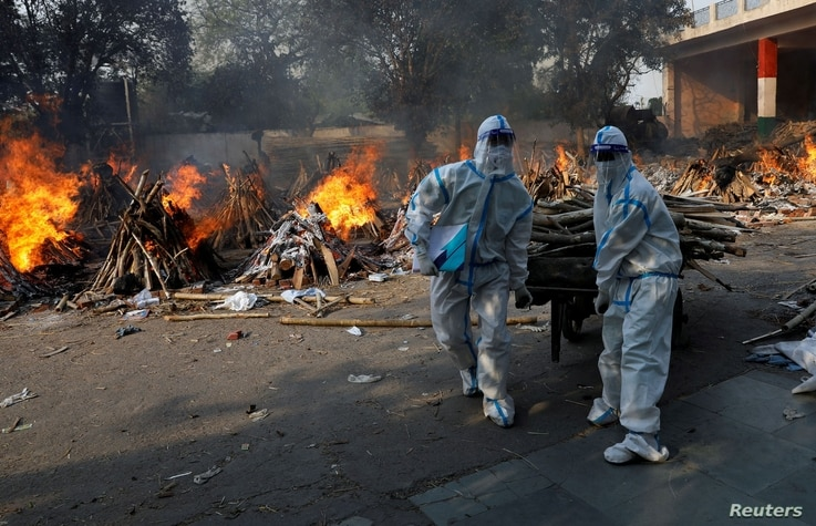 Health workers wearing personal protective equipment (PPE) carry wood to prepare a funeral pyre for a coronavirus disease …