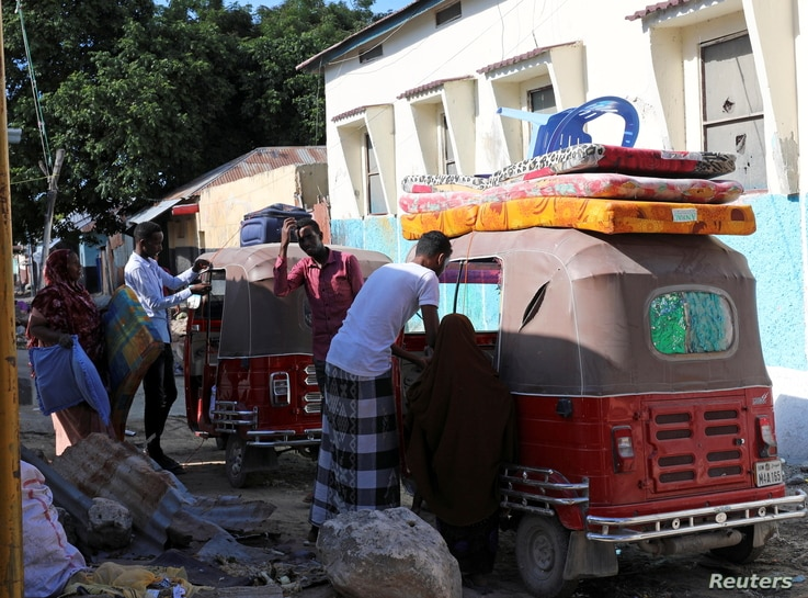 Residents load their belongings into rickshaws as they flee following renewed clashes between rival factions in the security…