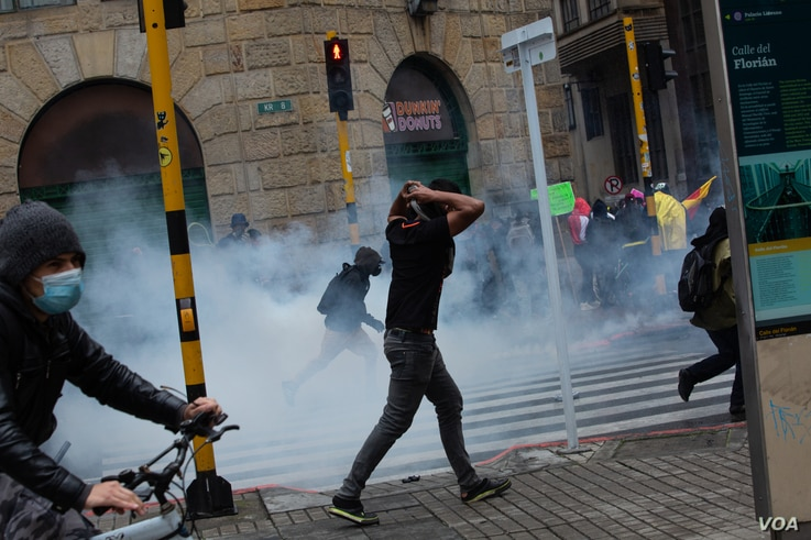 Demonstrators run away from tear gas during a national protest against tax reform in Bogotá, Colombia, April 28, 2021. (Pu Ying Huang/VOA)