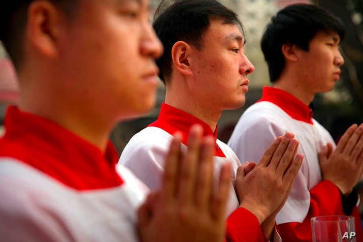 FILE - In this Saturday, March 31, 2018, file photo, Chinese acolytes pray during a Holy Saturday Mass on the evening before…