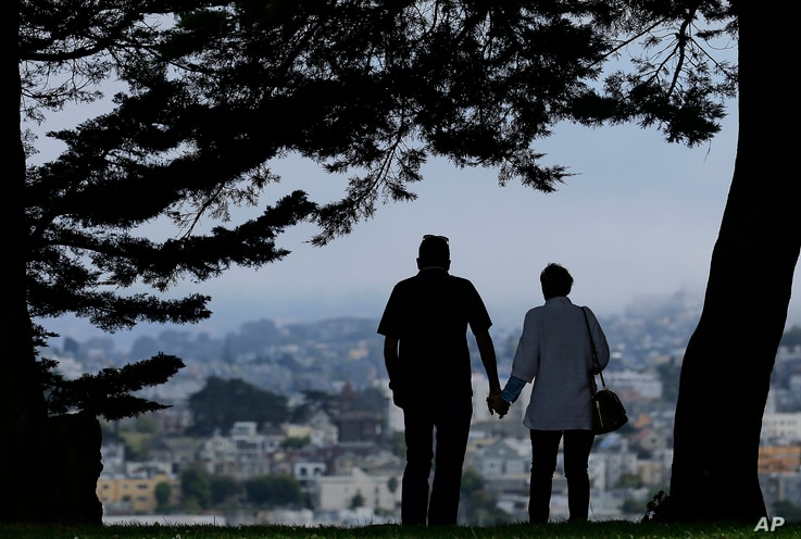 FILE - In this July 3, 2017 file photo, a man and woman walk under trees down a path at Alta Plaza Park in San Francisco. Data...