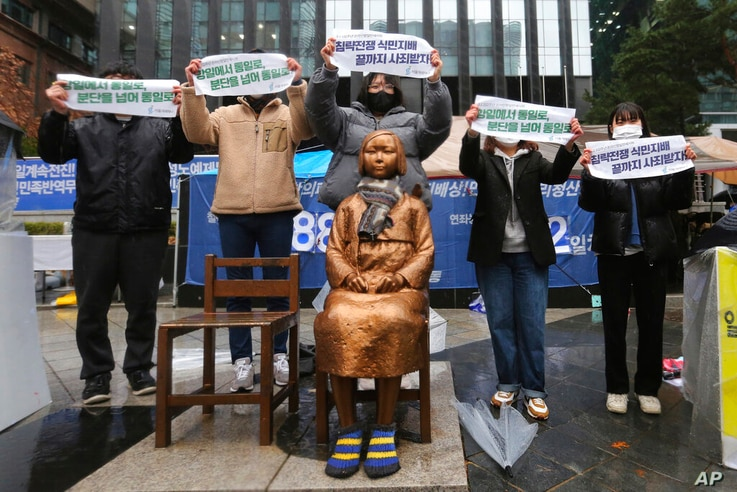 Protesters hold up banners during a rally to mark the March First Independence Movement Day against Japanese colonial rule, in...