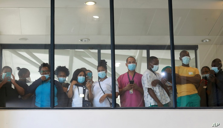 FILE - In this Feb, 17 2021 file photo, health care workers look through a window at a hospital in Khayelitsha, Cape Town,...