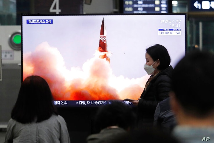 People watch a TV showing an image of North Korea's new guided missile during a news program at the Suseo Railway Station in…
