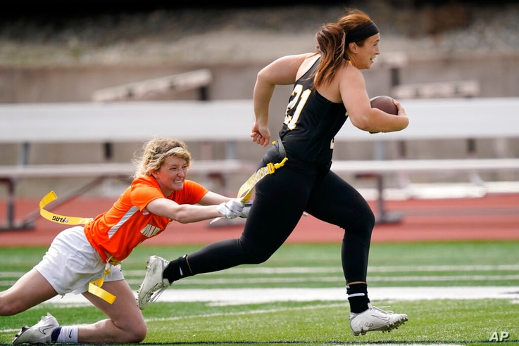 Ottawa quarterback Madysen Carrera (21) is tackled by Midland defender Casey Thompson, left, during an NAIA flag football game...