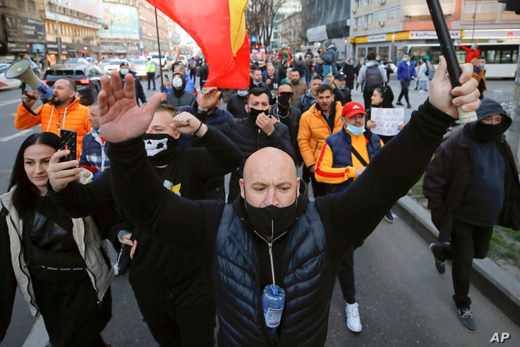 People protesting against the COVID-19 pandemic restrictions march in downtown Bucharest, Romania, Monday, March 29, 2021…