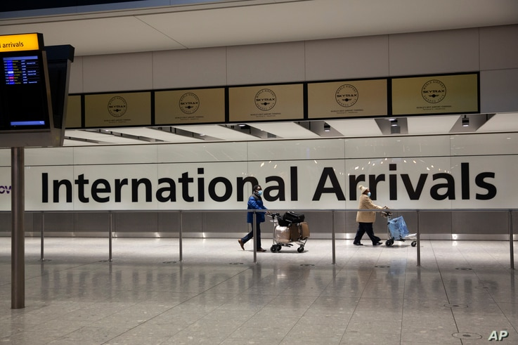 FILE - In this Tuesday, Jan. 26, 2021 file photo, arriving passengers walk past a sign in the arrivals area at Heathrow Airport…