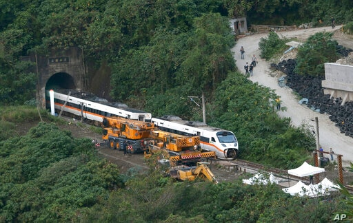 Rescue workers remove a part of the derailed train near Taroko Gorge in Hualien, Taiwan on Saturday, April 3, 2021. The train...