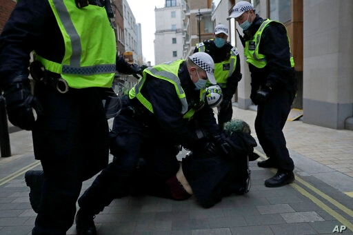 Police restrain a demonstrator during clashes following a 'Kill the Bill' protest in London, Saturday, April 3, 2021. The…
