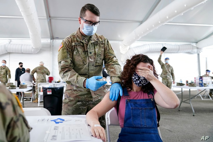FILE - In this April 5, 2021, file photo, Leanne Montenegro, 21, covers her eyes as she doesn't like the sight of needles,...