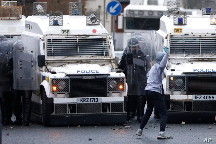 A Nationalist youth prepares to throw a projectile at a police line blocking a road near the Peace Wall in West Belfast,…