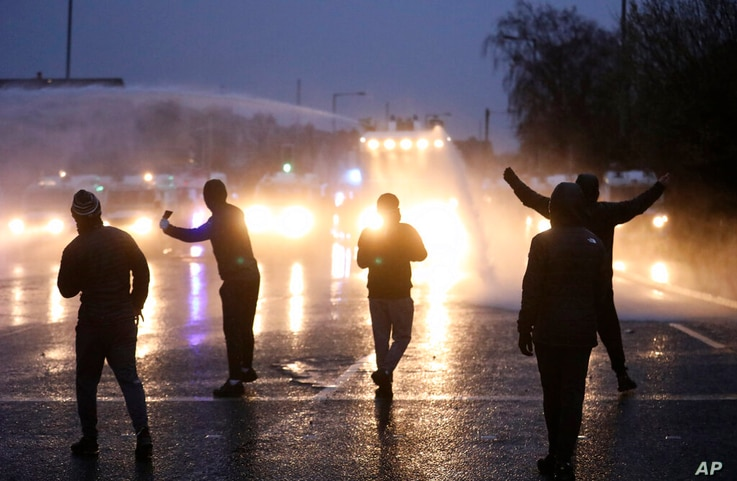Nationalist youths gesture towards a police line blocking a road near the Peace Wall in West Belfast, Northern Ireland,…
