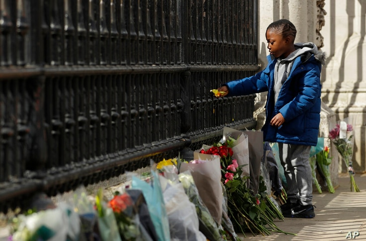A young boy places a flower on the gate at Buckingham Palace in London, after the announcement of the death of Britain's Prince…