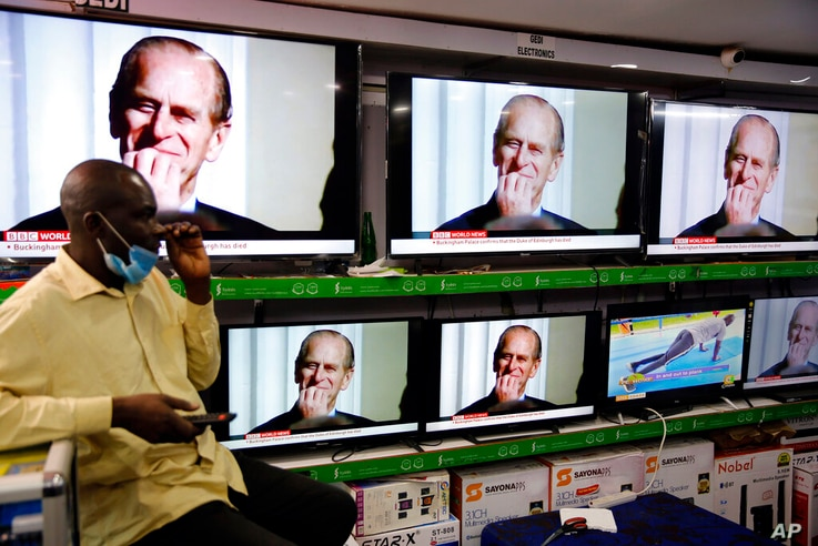 People watch the news announcing the death of Britain's Prince Philip in a shop in downtown Nairobi, Kenya, Friday, April 9,…