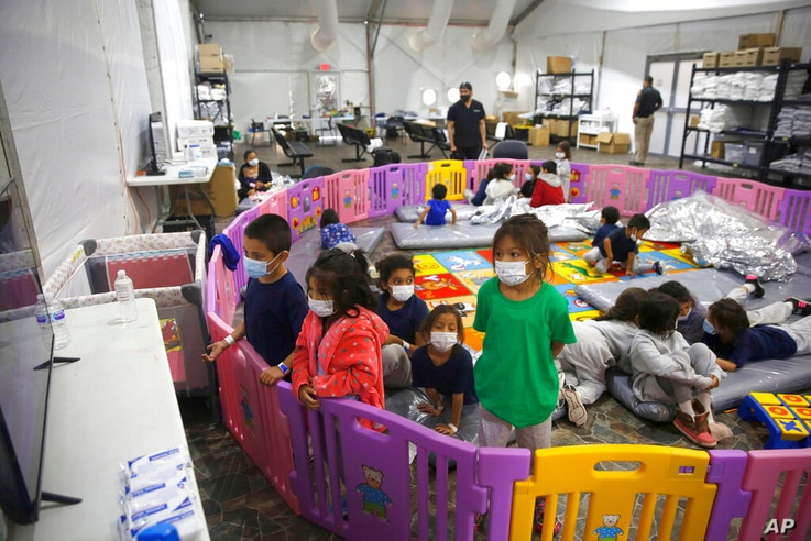 FILE - In this March 30, 2021, file photo, young unaccompanied migrants, from ages 3 to 9, watch television inside a playpen at...