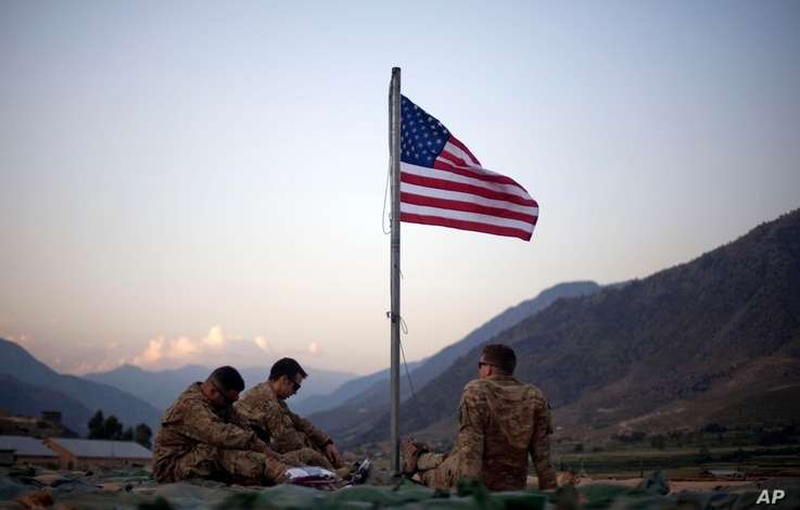 FILE - In this Sept. 11, 2011 photo, US soldiers sit beneath an American flag.