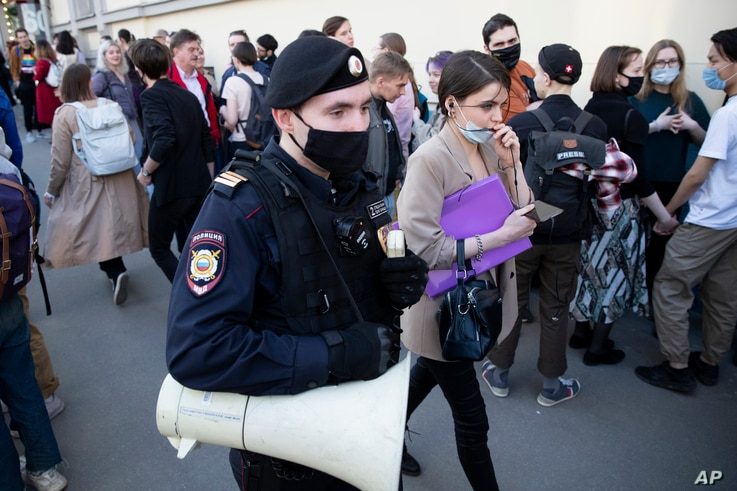 A police officer patrols an area as supporter of DOXA magazine editors gather at the court building in Moscow, Russia,…