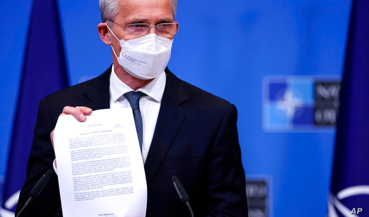 NATO Secretary General Jens Stoltenberg holds up a ministerial statement on Afghanistan as he attends a media conference at...