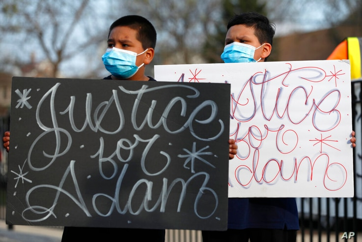 FILE - In this Tuesday, April 6, 2021, file photo, Jacob Perea, 7, left and Juan Perea, 9, hold signs as they attend a news…