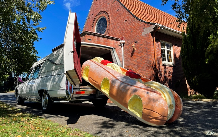 This photo provided by Ross Hall, shows a cream doughnut shaped coffin for the funeral of Phil McLean outside a church in…