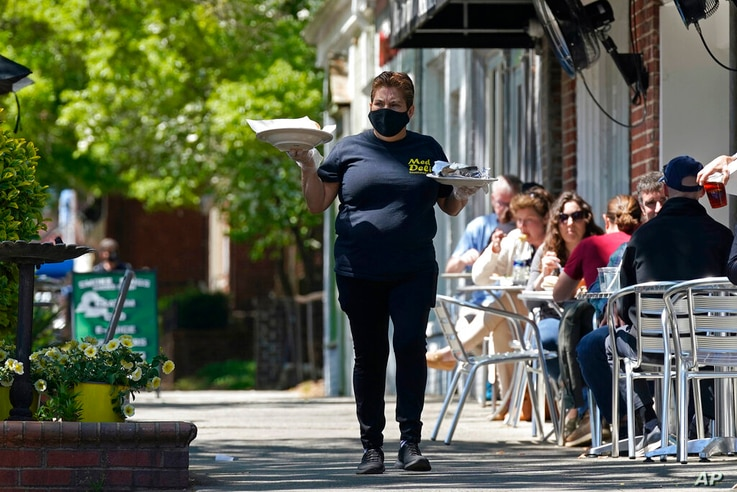 A member of the wait staff delivers food to outdoor diners along the sidewalk at the Mediterranean Deli restaurant in Chapel…