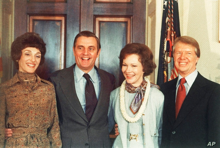 FILE - In this Jan. 21, 1977, file photo, President Jimmy Carter, right, and Rosalynn Carter, second from right, pose with Vice...